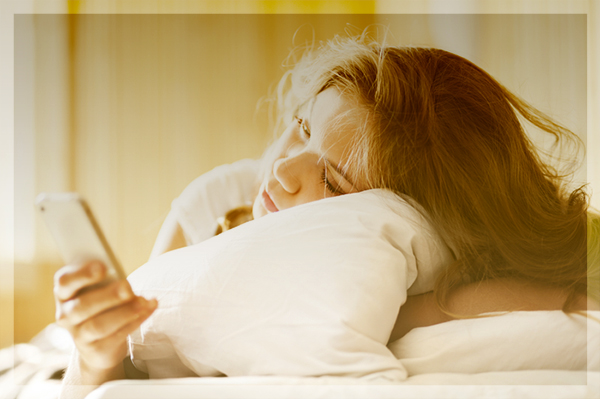 beautiful woman in bed with a smartphone